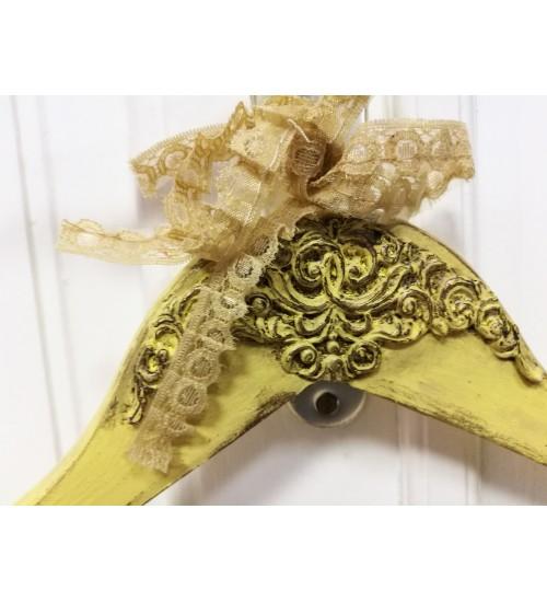 Kollane riidepuu ornamentide ja paelaga
